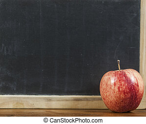 Back to school concept. Blackboard with apple on wooden de