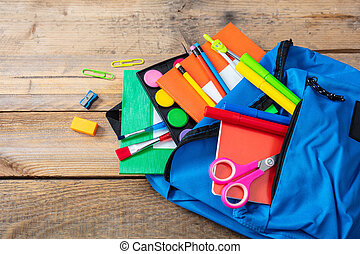 Blue backpack full of school supplies on wooden background, top view, copy space