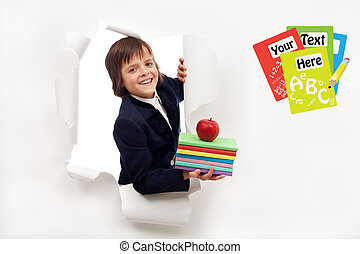 Back to school concept - boy with books looking through hole...