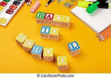 Back to school concept. Colored wooden alphabetical cubes on bright yellow background