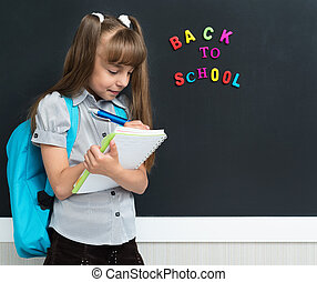Back to school concept. Happy schoolgirl with backpack and...