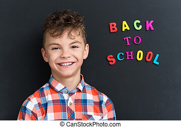 Back to school concept. Portrait of a schoolboy at the black...