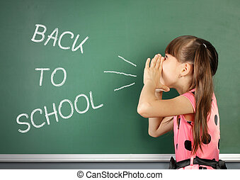 Back to school concept, school child shouting megaphone near school blackboard.