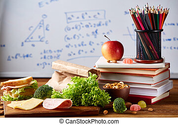 Back to School concept, school supplies, biscuits and lunchbox over white chalkboard, selective focus, close-up.