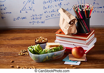 Back to School concept, school supplies, biscuits, packed lunch and lunchbox over white chalkboard, selective focus.