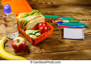 Back to school concept. School supplies, bottle of water, apple, banana and lunch box with sandwiches and fresh vegetables on a wooden desk