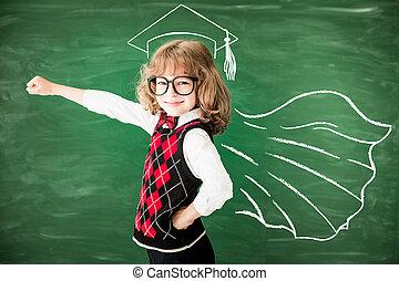 Back to school concept - Superhero school child in class....