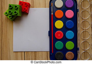 back to school concept watercolor palet flat lay with blank paper and building blocks
