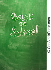 Back to school concept with written words in chalk on green blackboard. The beginning of the school year