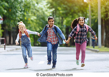 Back to school. Mixed Racial Group of happy elementary school students with backpacks running holding hands outdoors. Primary education concept.