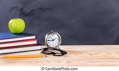 Back to school objects in front of erased black chalkboard