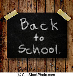 Back to school on message note with wooden background