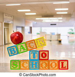 Back to School spelled out in wooden blocks with apple against corridor