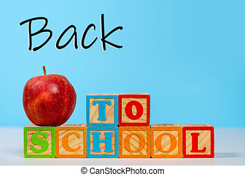 Back to School spelled out in wooden blocks with apple