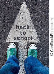 Back to school - Student standing above the sign back to...
