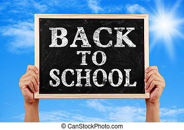 Back To School - Hands holding blackboard with text Back To...