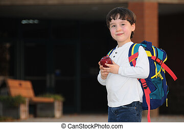 Back to School - A first grader pauses and smiles on his way...