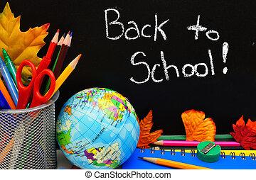 Back to School written on a blackboard with school supplies