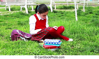 Back to School - Schoolgirl in the park. She is sitting down...
