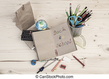 Back to school template with school stationery and lunch bag on table