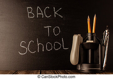Back to school, the concept of parenting. The inscription on the blackboard with white chalk, next to it is a stand for pens with stationery. Place for text. Copy space