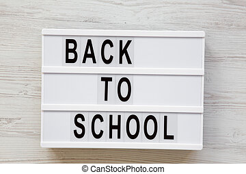 'Back to school' word on lightbox over white wooden surface, from above. Top view, overhead.