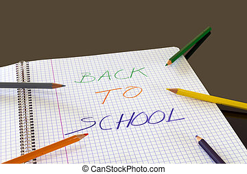 Back to school written in color on book, with colored pencils around