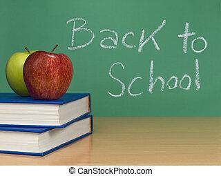 Back to school written on a chalkboard. Two apples over...