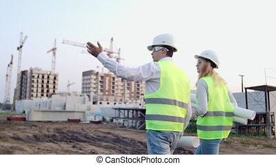 Back turned engineer and controller at construction site reviewing office blueprints and technical drawings walk and discussing