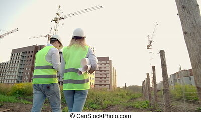 Back turned engineer and inspector at construction site reviewing office blueprints and technical drawings walk and discussing