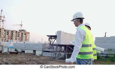 Back turned engineer and technician at construction site reviewing office blueprints and technical drawings walk and discussing