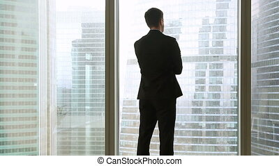 Back view at businessman in suit standing near full-length window