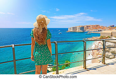 Back view beautiful girl looking at the old town of Dubrovnik in Croatia, Europe. Summer holidays on Mediterranean sea.