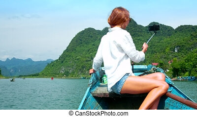 back view blond woman makes selfie sailing on river boat