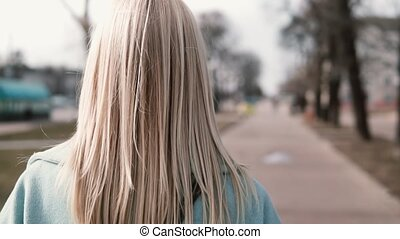 Back view blonde woman walking and looking left. Caucasian girl in blue coat with beautiful long fair hair. Slow motion.