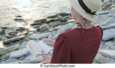 Back view Close-up An attractive Caucasian girl in a red bright dress and a straw hat sits on a large stone by the sea at sunset and reads an interesting book