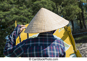 Back view closeup of old vietnamese woman on the boat wearing conical straw hat.