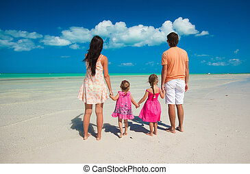 Back view family of four on caribbean beach vacation