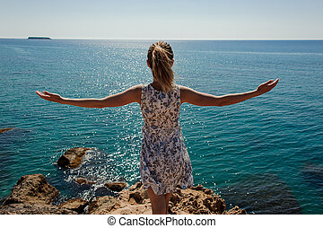 Back view girl standing on the rock in dress with a open hands
