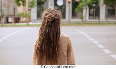 back view girl with dreadlocks standing on the street