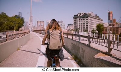 Back view happy girl with flying dark hair riding a bicycle along a separate bike lane in New York City slow motion.