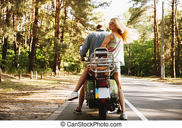 Back view image of young man on scooter with girlfriend.