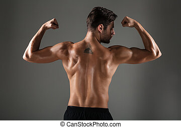 Back view image of young sports man showing biceps