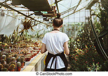 Back view image of young woman standing in greenhouse