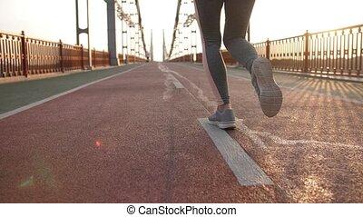 Back view legs of runner female on bridge