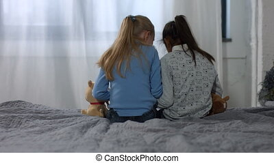 Back view little multi ethnic girls sitting on bed
