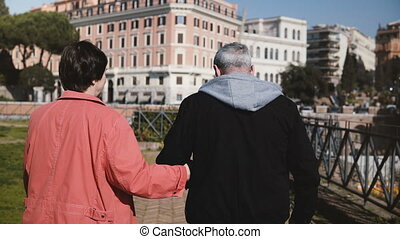 Back view lovely romantic senior happy couple walking together holding hands on vacation in early autumn Rome, Italy.