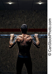 Back view male muscular athlete doing pull up
