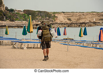 Back view man walking with a hiking backpack on the sea coast