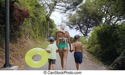 Back view. Mom and two sons are walking in the park by the sea. A young woman in a swimsuit and a big hat along with children walks to the park near the sea